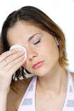 Removing make up. Young girl removing make up with cleanser and cotton pad Stock Photos
