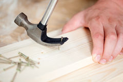 Removing nail from wooden plank using hammer Stock Image