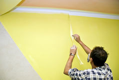 Removing paint tape. A man painting a room in yellow, removing a painting tape protecting the corner where the paint is white Royalty Free Stock Images