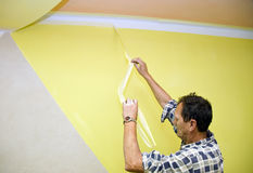 Removing paint tape. A man painting a room in yellow, removing a painting tape protecting the corner where the paint is white. HOME BUILDING & RENOVATION royalty free stock photos