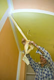 Removing paint tape. A man painting a room in yellow and orange, removing a painting tape protecting the corner where the paint is white. HOME BUILDING & stock photography