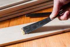 Removing paint from a wood surface. Using a spackle knife Stock Photos