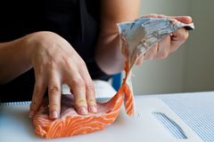 Removing salmon skin Royalty Free Stock Image