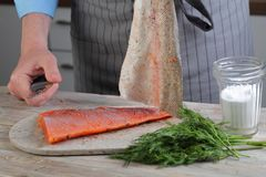 Removing skin from salted salmon Royalty Free Stock Photo