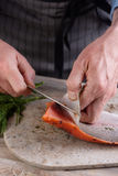 Removing skin from salted salmon Stock Photography