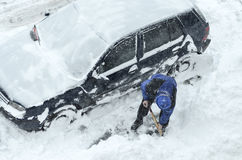 Removing snow from the cars Royalty Free Stock Images