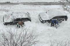 Removing snow from the cars Royalty Free Stock Photography