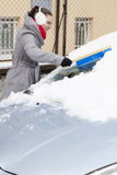 Removing snow and ice from the car Royalty Free Stock Photo