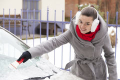Removing snow and ice from the car. Smiling cute woman removing snow and ice from the car windshield Stock Photo