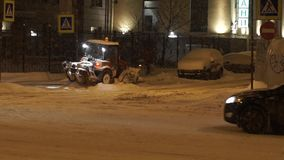 People and cars moving along street at night in heavy snow in winter. stock video footage