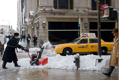Removing snow after the storm in New York City. A store employee removes the snow in 5th Avenue, Manhattan, New York City Royalty Free Stock Images