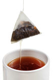 Removing of tea bag from cup with brewing tea Royalty Free Stock Photo