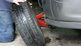 Removing an old tire from car. Removing tire from gray car with red jack near stock video footage