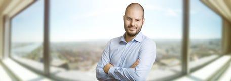 Remplaçant de sourire réussi d'homme devant la fenêtre d'un skyscrapper Concept d'immobiliers, d'affaires et de succès photo libre de droits