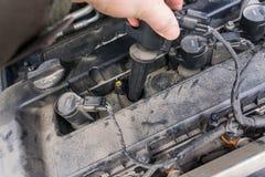 Remplacement de la bobine d'allumage et des bougies d'une vieille voiture sale Image libre de droits