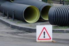 Remplacement des tuyaux dans la ville Grands nouveaux tuyaux Signe d'attention image stock
