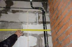 Remplacement du câblage dans la maison, appartement ruban métrique de mesure photos stock
