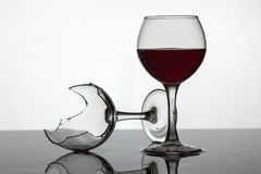Rempli de verre de vin et de verre de vin cass? avec le vin rouge image libre de droits