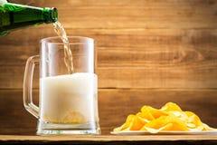 Remplir verre de la bière sur le fond d'un mur en bois Image stock