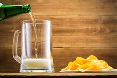 Remplir verre de la bière sur le fond d'un mur en bois Photo stock