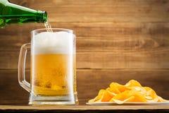 Remplir verre de la bière sur le fond d'un mur en bois Photos stock