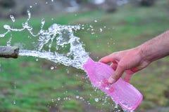 Remplissez à partir de l'eau de source naturelle images stock
