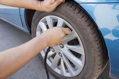 Remplissez air dans un pneu de voiture Images stock