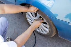 Remplissez air dans un pneu de voiture Photos stock