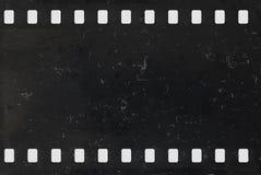 Remsa av den gamla negativa celluloidfilmen med damm och skrapor arkivfoton