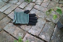 Remsahandskar lägger på det utomhus- tegelstengolvet royaltyfri fotografi