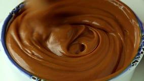 Remuant le caramel liquide avec la cuillère en bois, fin  clips vidéos