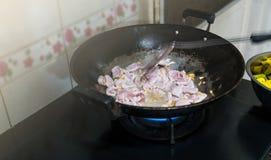 Remuez et faites frire le porc est fait dans la cuisine Afin de faire cuire S photos libres de droits