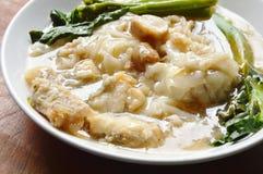 Remuez la nouille de riz frit avec les poissons bas et le chou frisé chinois en sauce à sauce au jus de plat photo libre de droits