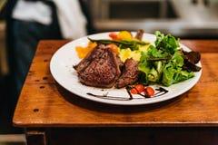 Remuez le bifteck de boeuf frit servi avec l'écrimage végétal de garniture et de salade avec le habillage balsamique images libres de droits