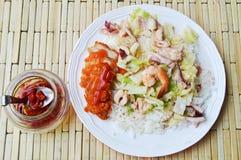 Remuez le chou frit avec des fruits de mer et le poulet croustillant sur le riz Photos libres de droits