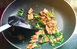 Remuez le porc et le basilic frits dans une pelle chaude de casserole et de plastique image stock