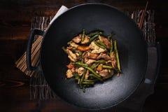 Remuez le poulet frit dans le wok de fonte photos libres de droits