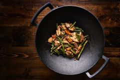 Remuez le poulet frit dans le wok de fonte images libres de droits