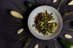 Remuez les l?gumes frits dans un wok sur la table fonc?e image stock