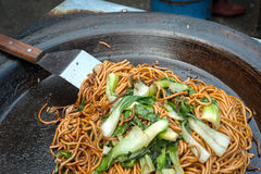 Remuez les nouilles frites à un marché en plein air chinois photo libre de droits