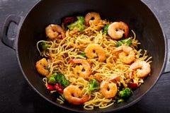 Remuez les nouilles frites avec des crevettes et des légumes dans un wok photo libre de droits