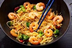 Remuez les nouilles frites avec des crevettes et des légumes dans un wok photographie stock libre de droits