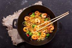 Remuez les nouilles frites avec des crevettes et des légumes dans un wok photo stock