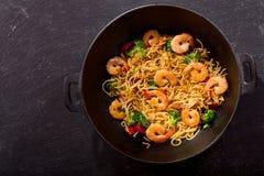 Remuez les nouilles frites avec des crevettes et des légumes dans un wok images stock