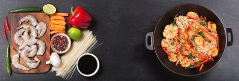 Remuez les nouilles frites avec des crevettes et des légumes dans un wok avec des ingrédients pour faire cuire, vue supérieure image libre de droits