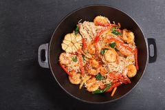 Remuez les nouilles frites avec des crevettes et des légumes dans un wok, vue supérieure photo stock