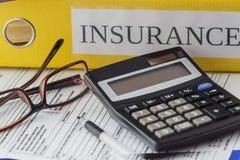 Ren försäkringform, mappar, exponeringsglas, räknemaskin och en penna royaltyfri foto