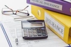 Ren försäkringform, mappar, penna, exponeringsglas och räknemaskin fotografering för bildbyråer