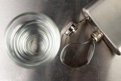 Ren kall vodka i ett exponeringsglas Metallbröst och spilld alkohol på den skinande stångöverkanten arkivfoto