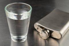 Ren kall vodka i ett exponeringsglas Metallbröst och spilld alkohol på den skinande stångöverkanten royaltyfria foton